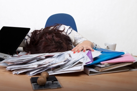 Young female office worker sleep at a desk with a pile of papers Stock Photo