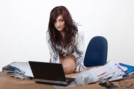Young female office worker sitting at desk, working on computer photo
