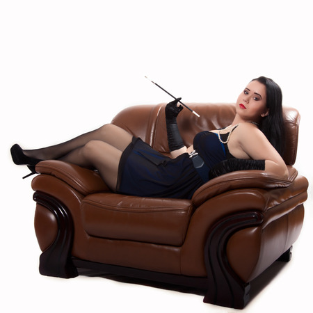 Young woman in retro clothing lying in a big chair with a cigarette holder, on white background photo