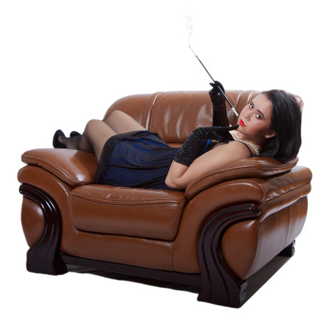 Young woman in retro clothing lying in a big chair with a cigarette holder, on white background