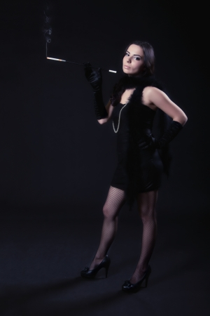 Young woman in retro dress with cigarette holder posing on a dark background