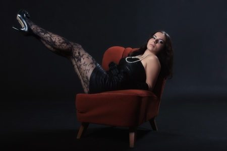 Young woman in retro dress rises legs on an old chair on dark background photo
