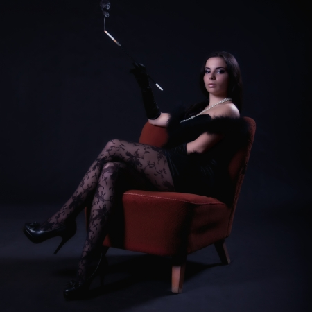 Young woman in retro dress with cigarette holder sitting on an old chair on dark background