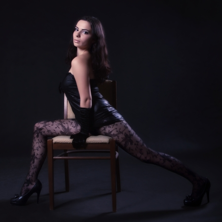 Young woman in leather dress and patterned stockings makes spread eagle on the chair