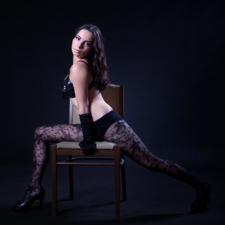 Young woman in bra and patterned stockings makes spread eagle on the chair photo