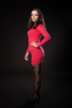 Young woman in pink dress posing on a dark background photo
