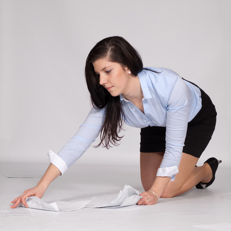 Young woman in mini skirt and blouse, on her knees raised from the ground fallen documents photo