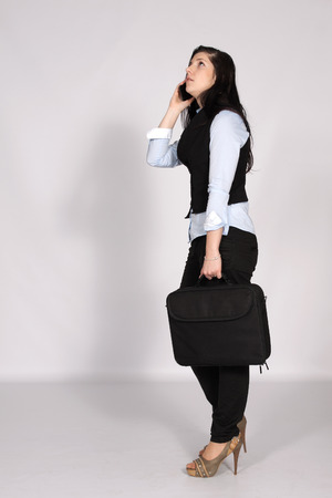 Young woman standing with laptop bag and phone