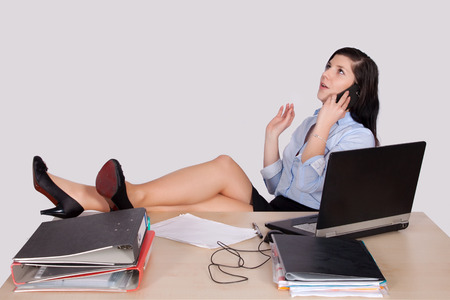 explains: Young female office worker with feet on desk phone and explains Stock Photo