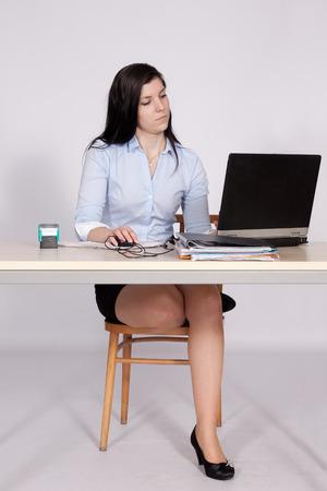 belles jambes: Jeune femme travaillant derrière un employé de la réception à l'ordinateur portable, avec un pied sur une chaise
