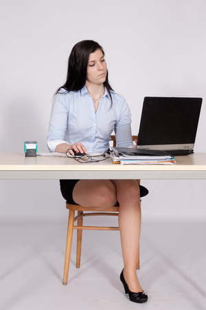 Young woman working behind a desk clerk at the laptop, with one foot on a chair photo