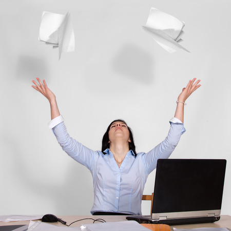 Young woman sitting at table with laptop and throws out the paper in the air