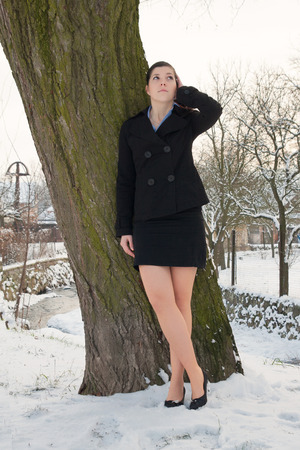 mini dress: Young woman in mini costume, standing in pumps in winter on snow in front of a tree