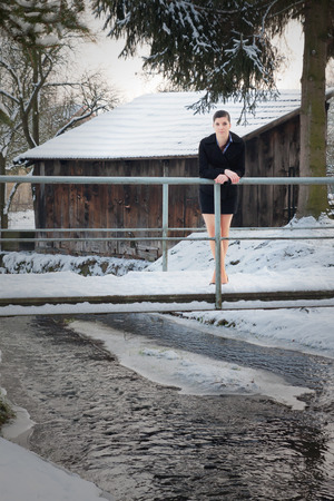 Young woman in mini costume, standing in pumps in the winter on a bridge over the brook