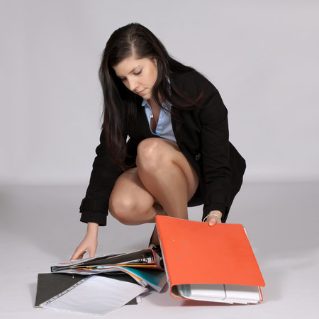 skirt up: Young woman in mini costume, squatting rises from the ground fallen documents Stock Photo