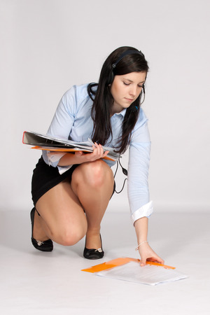 Young woman in mini skirt and blouse, squatting rises from the ground fallen documents  and in addition she call up
