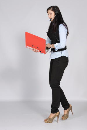Young woman with headset phone while walking and holding hands a pile of documents photo