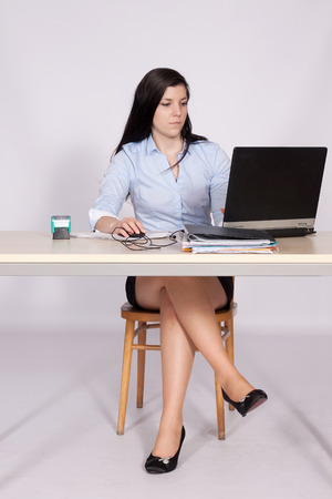 crossed legs: Young woman working behind a desk clerk at the a laptop with legs crossed