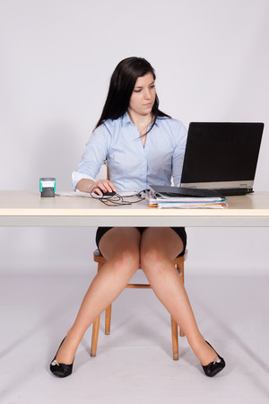Young woman working behind a desk clerk at the a laptop with legs in the shape of A photo