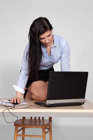 pies bonitos: Mujer joven que trabaja detrás de una recepcionista en el portátil, de rodillas en el mostrador