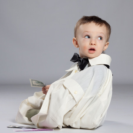 Boy toddler businessman, sitting next to a pile of money dressed in grown-shirt with bow tie, holding in hand the dollars Stock Photo
