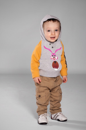 Toddler boy standing in the Easter Bunny sweatshirt with a hood on his head and sneakers Stock Photo