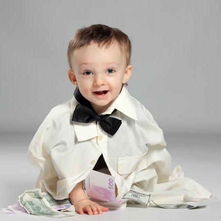 Boy toddler businessman sitting dressed in grown-shirt with bow tie, in front of him has a pile of money and enjoys Stock Photo