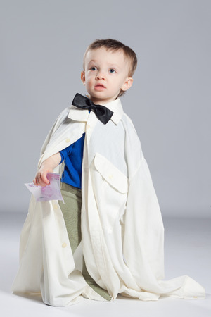 Boy toddler businessman, standing dressed in grown-shirt with bow tie, hand holding euro Stock Photo