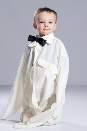 Boy toddler businessman, standing dressed in grown-shirt with bow tie photo