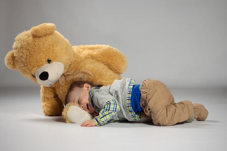 Boy toddler lying and snuggle to a large teddy bear photo