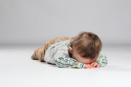 Vermoeide peuter jongen liggend op de grond met zijn gezicht naar beneden Stockfoto