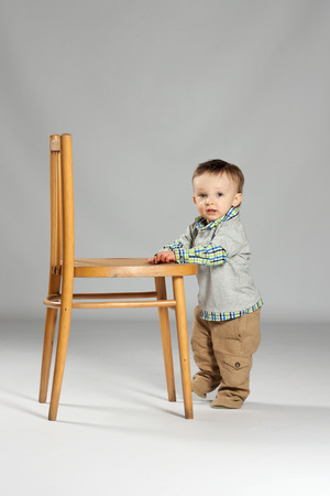 disobedience: Toddler boy standing beside a big wooden chair