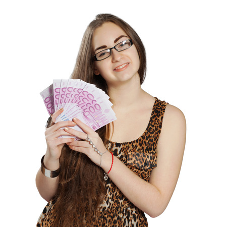 Long-haired teenager girl in leopard dress holds euros in hand in a fan-shape, isolated on white