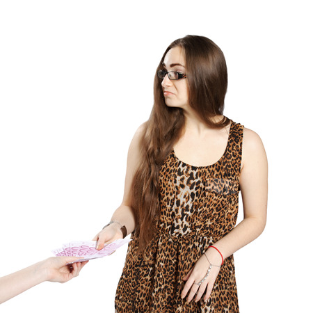 Long-haired teenager girl in leopard dress accepts a bribe in euro, isolated on white  photo