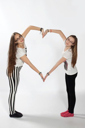 Two sisters created using your hands shape of a large heart