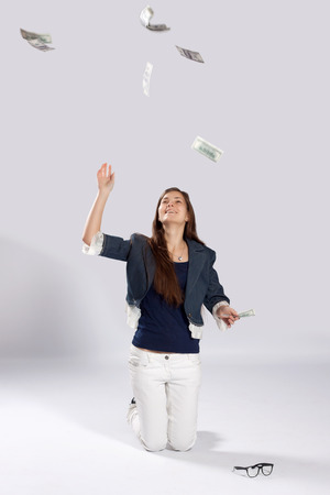 Young long-haired woman kneeling on the floor and throws dollars up to photo