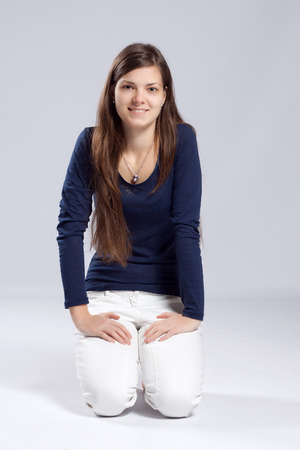 Young long-haired woman without makeup in white jeans and a blue shirt, kneels on the floor photo