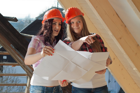 accordance: Two young women workers standing on under construction roof, and control building in accordance with drawing
