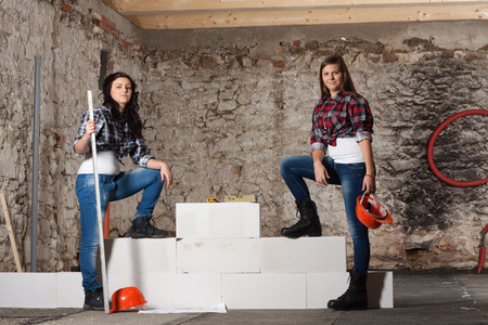Two young long-haired woman repairing the old house and build a new wall from blocks in accordance with drawing photo