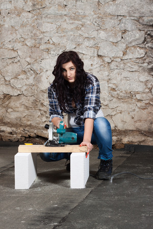 workwoman: Young long-haired woman with a circular saw cuts wood at repair of an old house