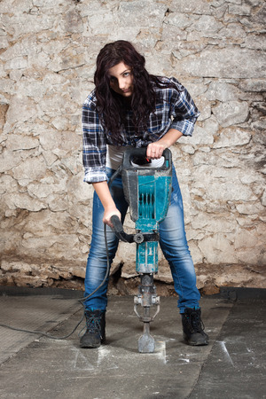 Young long-haired woman working with jackhammer during the repair an old house photo