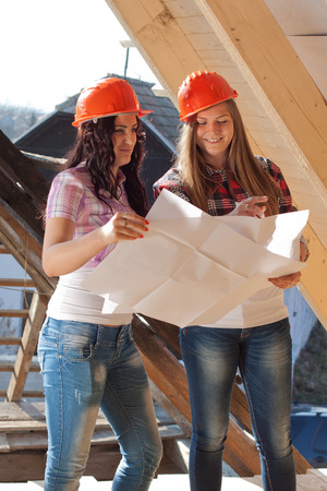 Two young women workers standing on under construction roof, and control building in accordance with drawing photo