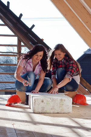 Two young women workers sitting on under construction roof, and control building in accordance with drawing photo