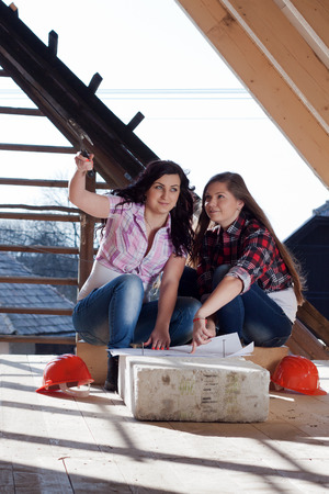 accordance: Two young women workers sitting on under construction roof, and control building in accordance with drawing Stock Photo
