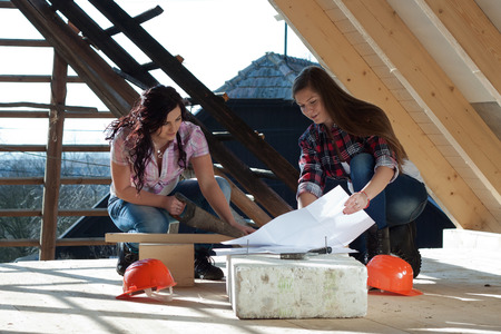 Two young long-haired woman sawed wood for the roof of the house in accordance with drawing photo