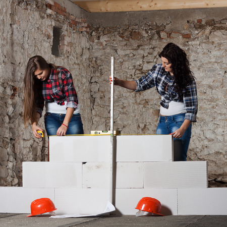 accordance: Two young long-haired woman repairing the old house and build a new wall from blocks in accordance with drawing