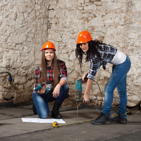 Two young long-haired woman works to repair an old house with an electric drill and cordless screwdriver photo