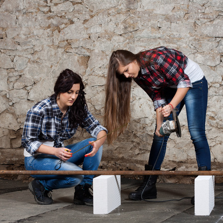 Two young long-haired woman cut iron pipe with angle grinder during the repair an old house photo