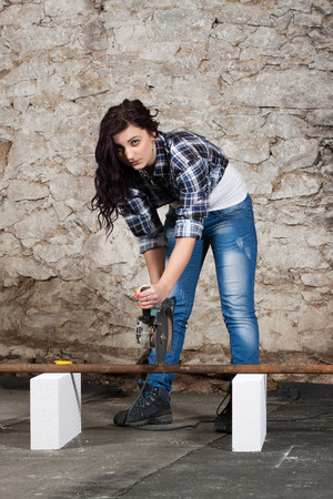 Young long-haired woman cut iron pipe with angle grinder during the repair an old house photo