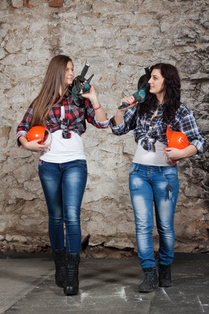 Two young long-haired woman with a drill on the shoulder leave from work photo